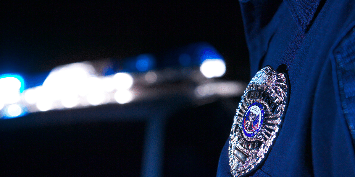 image of police badge on uniform shirt