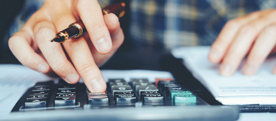 man using calculator and notepad